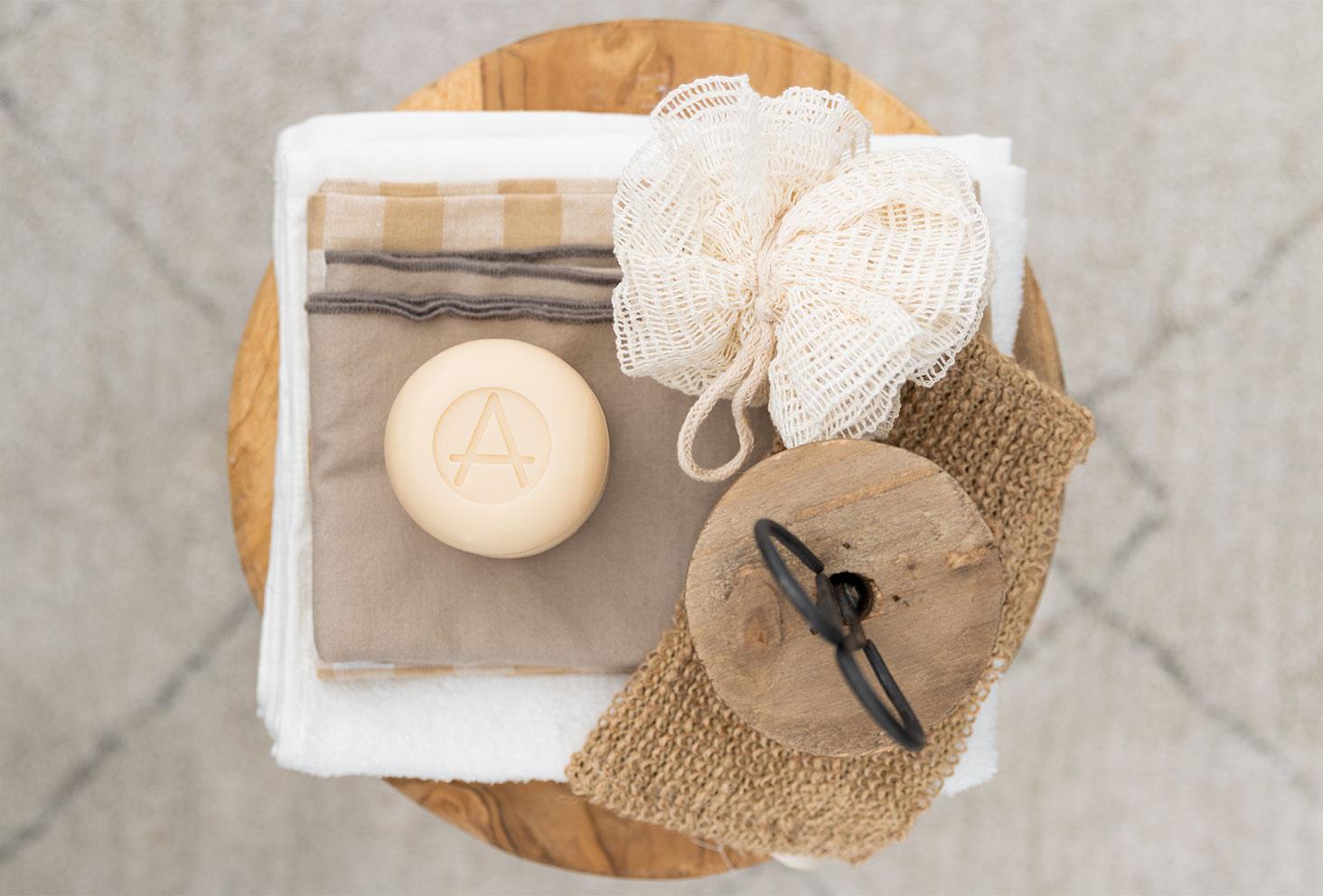 Le savon à l'amande et au lait de chèvre de la marque Soin Amalthée sur un tabouret en bois dans une ambiance de salle de bain