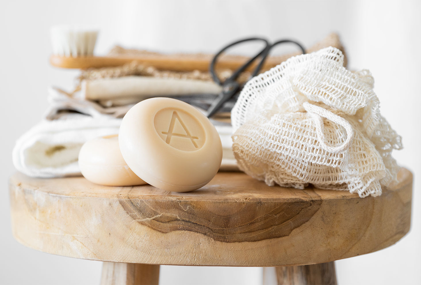 Le savon au lait de chèvre et à l'odeur d'amande Soin Amalthée sur un tabouret rond en bois dans une salle de bain