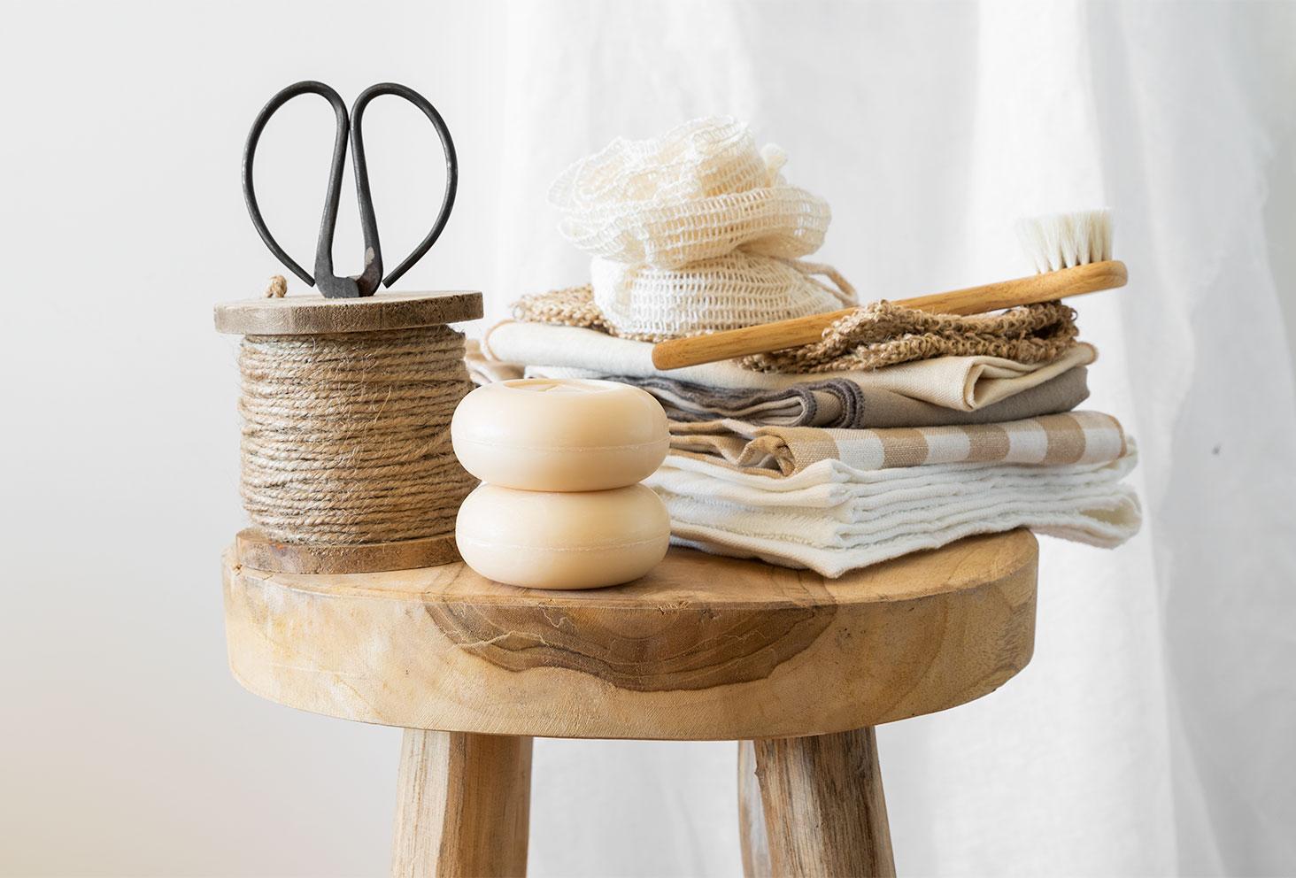 Deux savons de la marque Soin Amalthée spécialisée dans les produits au lait de chèvre, l'un sur l'autre posé sur un tabouret en bois dans une salle de bain