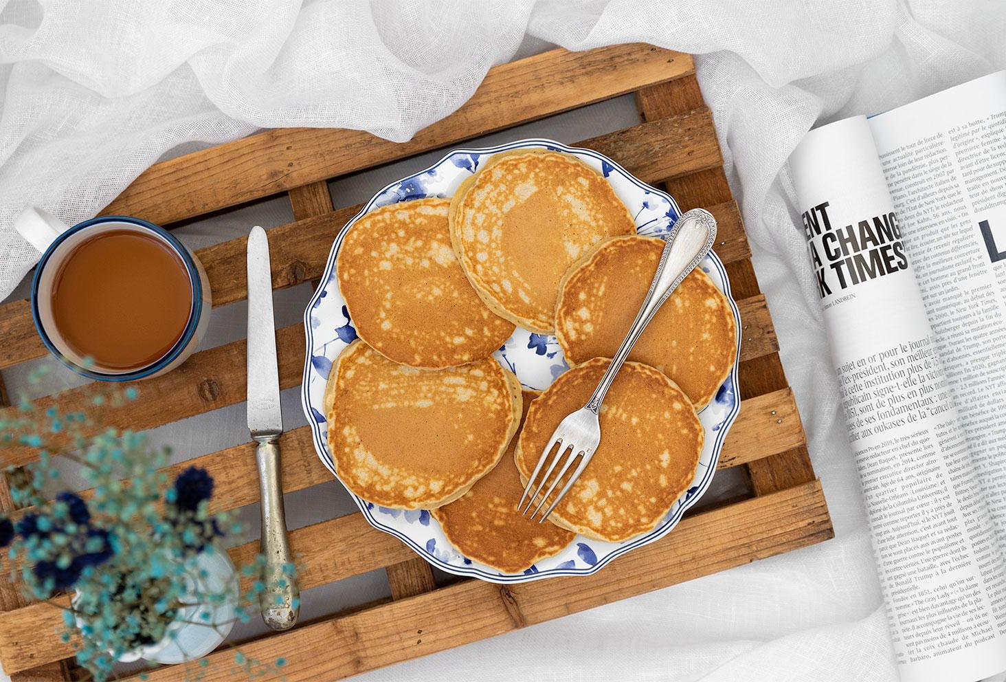 Zoom sur une assiette vintage pleine de pancakes moelleux et healthy à la banane, posé sur un plateau en bois sur un lit, avec un magazine et une tasse de thé