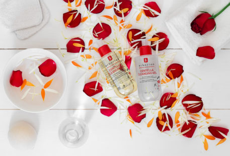 L'huile démaquillante et le gel nettoyant doux Erborian allongés sur un lit de pétales de fleurs fraîches dans une salle de bain