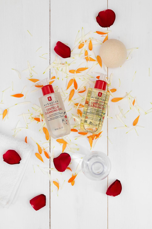 Les 2 produits pour un double nettoyage par Erborian, sur une table en bois blanc au milieu de pétales de fleurs
