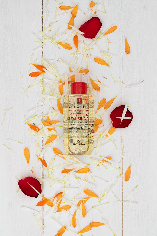L'huile démaquillante à la Centella Asiatica d'Erborian allongé sur un lit de pétales de fleurs et de roses fraîches, sur une table en bois blanc