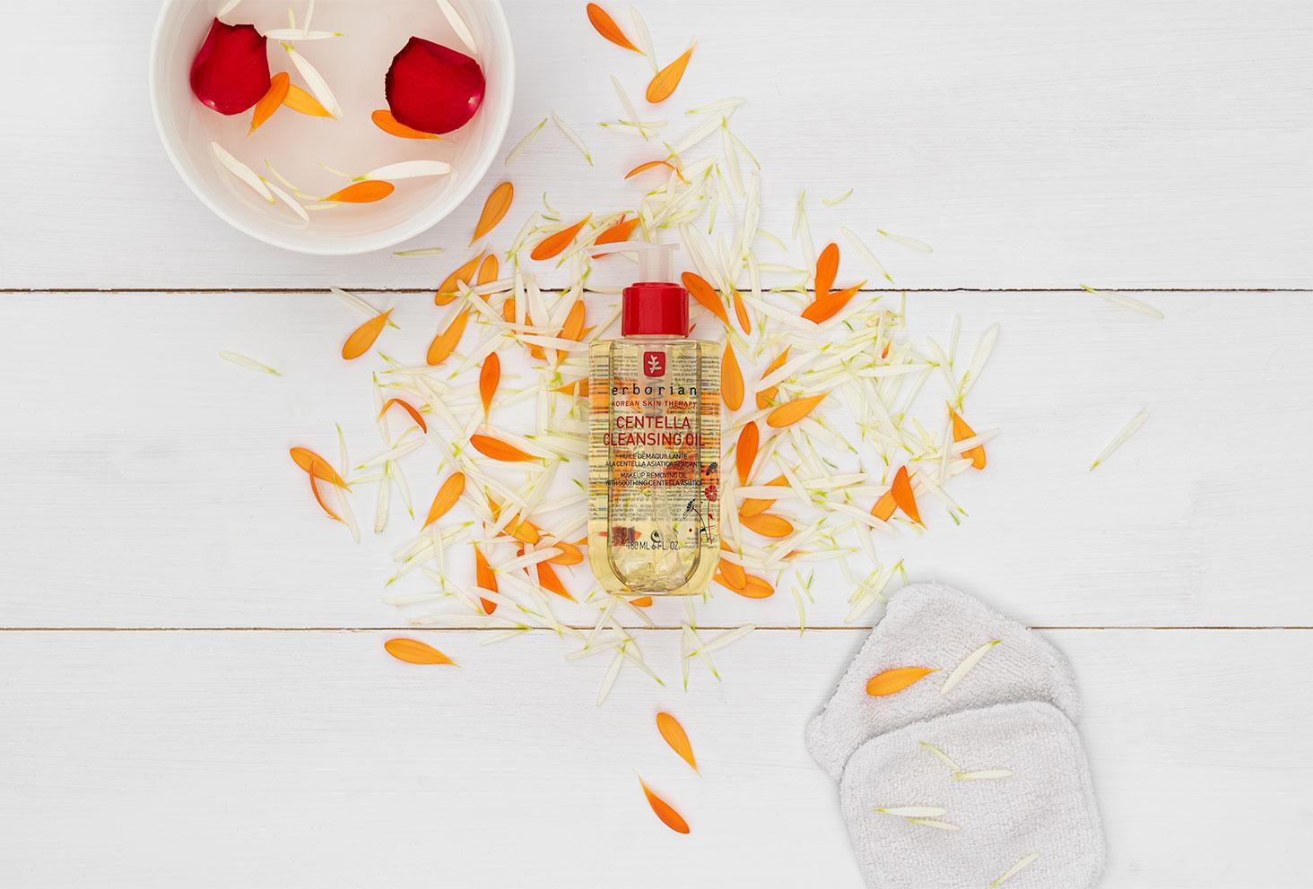 Zoom sur l'huile démaquillante Erborian, posé au milieu de pétales de fleurs fraîches