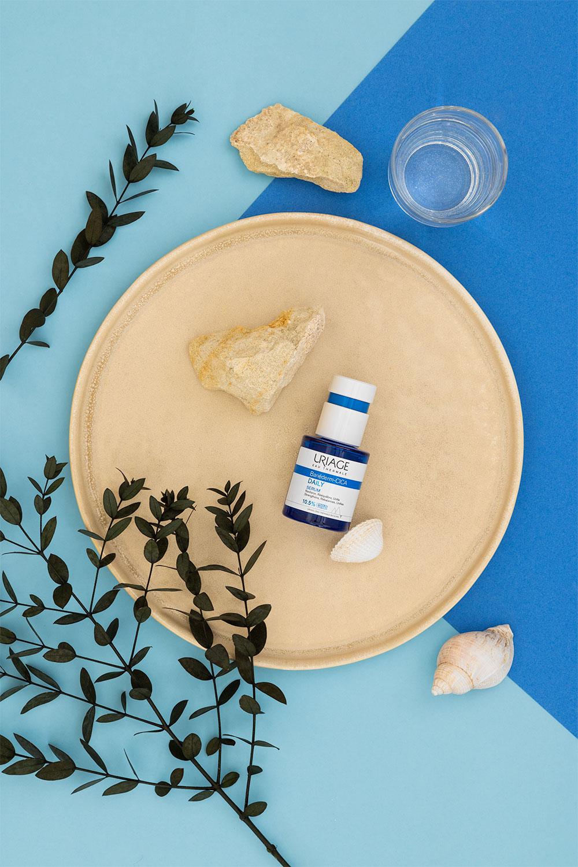 Le daily sérum hydratant Uriage dans une assiette ronde avec des pierres et des coquillages, sur un fond bleu ciel
