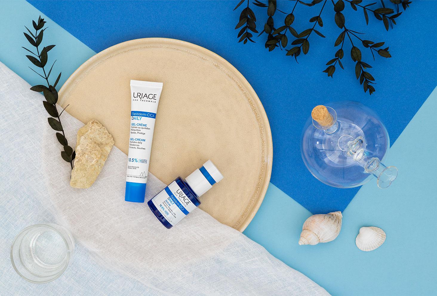 La gamme Bariéderm-CICA Uriage dans une assiette ronde avec des pierres et des coquillages, sur un fond bleu avec des branches d'eucalyptus
