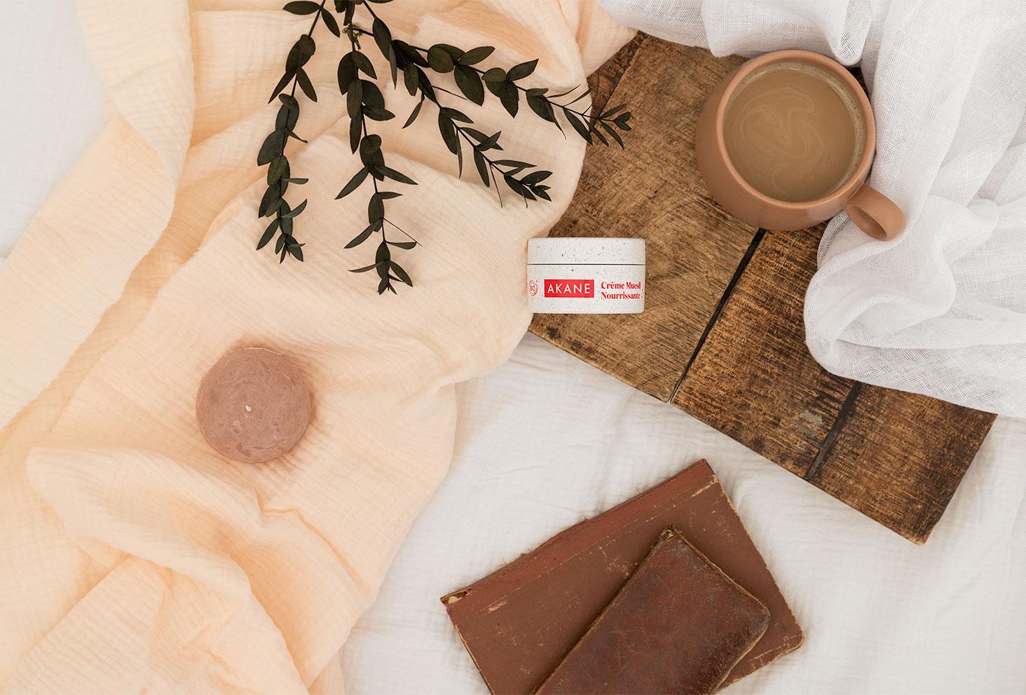 Crème nourrissante Akane sur un lit, avec un plateau et une tasse de cappuccino, pour le petit déj