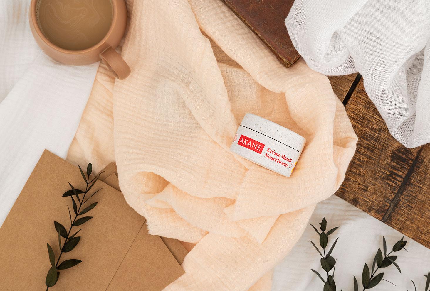 Zoom sur la crème muesli nourrissante de la marque naturelle Akane, posée sur un linge crème avec le petit déjeuner