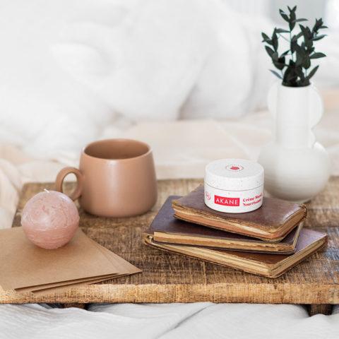 La crème muesli noourrissante Akane sur une pille de livre posée sur un lit