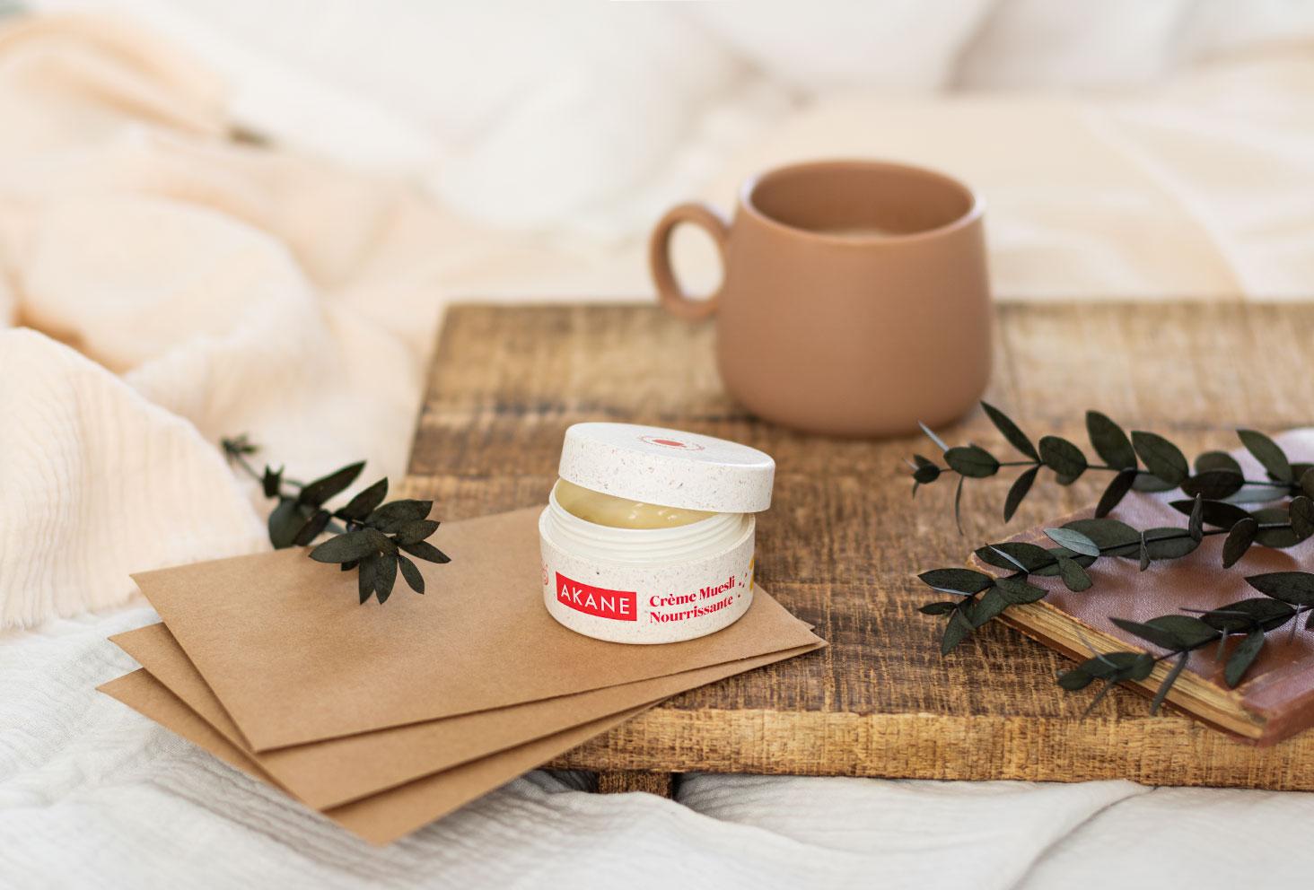 La crème muesli nourrissante de la marque Akane ouverte, posée sur un plateau sur un lit pour le petit déjeuner