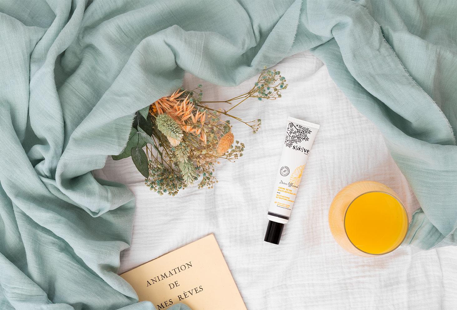 La crème SPF30 de Saeve posée sur un drap blanc avec un livre de poésie et un verre de jus d'orange pour l'été