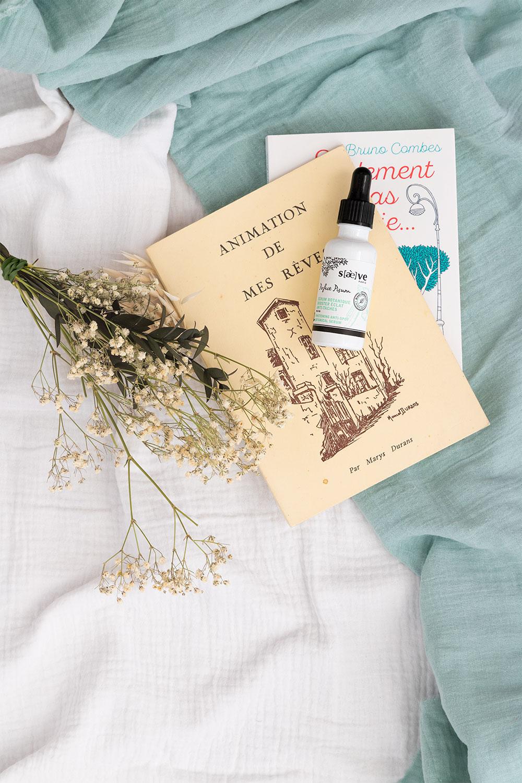Le sérum de Saeve sur un drap blanc avec un bouquet de fleurs et des bouquins pour l'été
