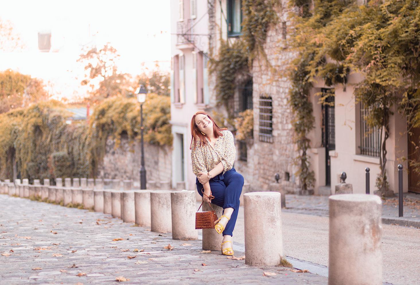 Assise dans une ruelle pavée de Montmartre avec le sourire, sur un plot de béton, en chemisier jaune et pantalon bleu