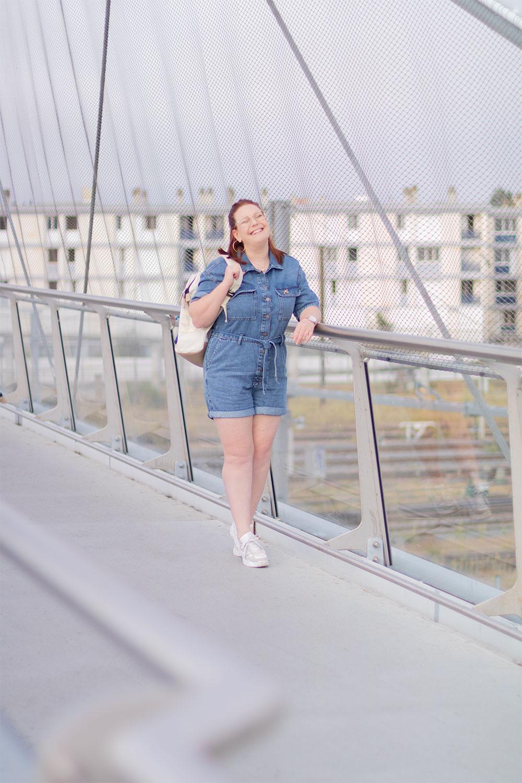 Sur un pont en combishort en jean et baskets, un sac à dos sur l'épaule, avec le sourire