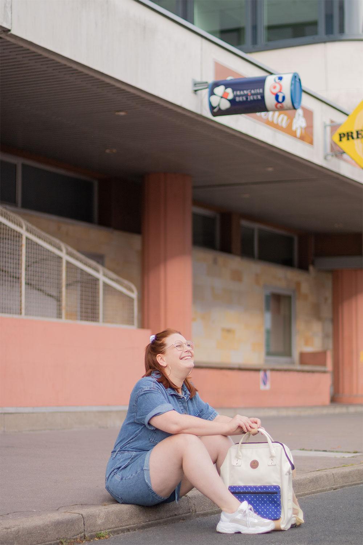 Assise sur un trottoir dans la rue en combishort avec un sac à dos et des baskets