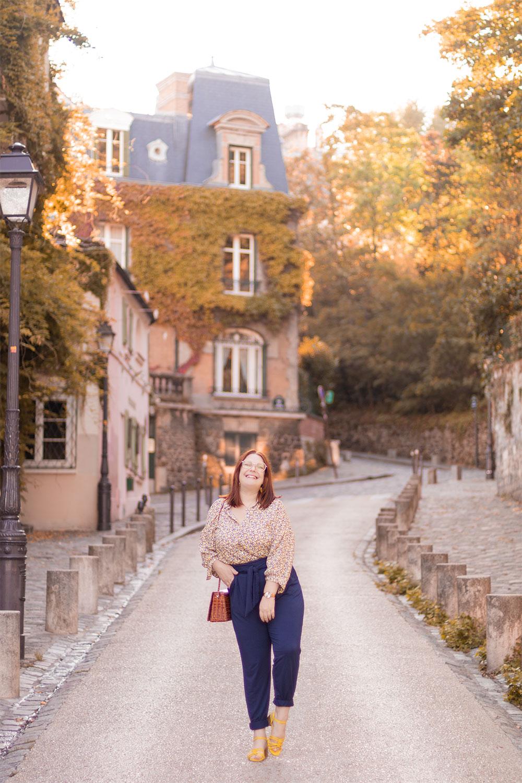 Dans une grande rue pavée de Montmartre, avec le sourire, en pantalon bleu et chemisier jaune