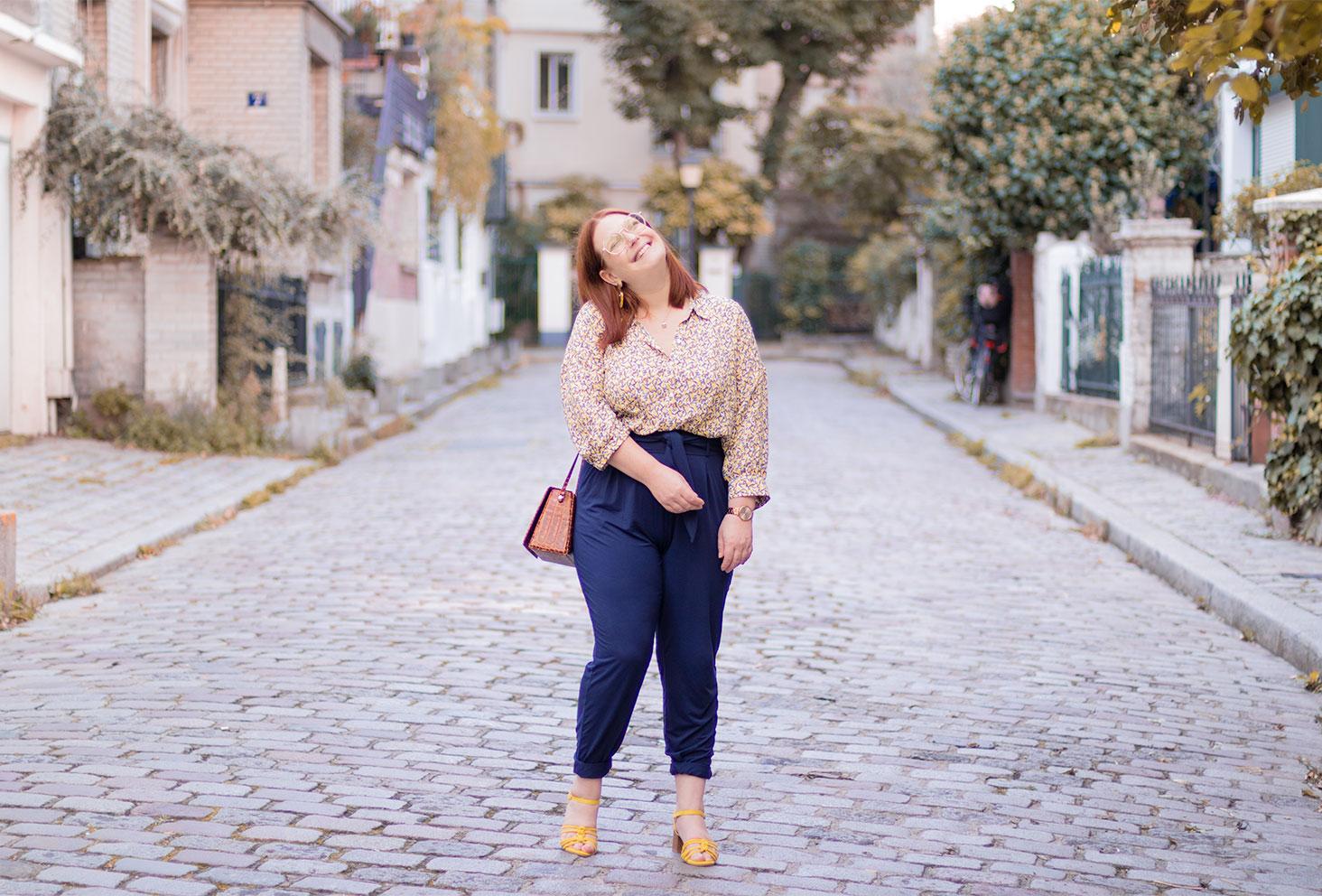 Au milieu d'une ruelle pavée de Montmartre avec le sourire, en pantalon bleu et talons jaunes, le sac Cavale Paris sur l'épaule