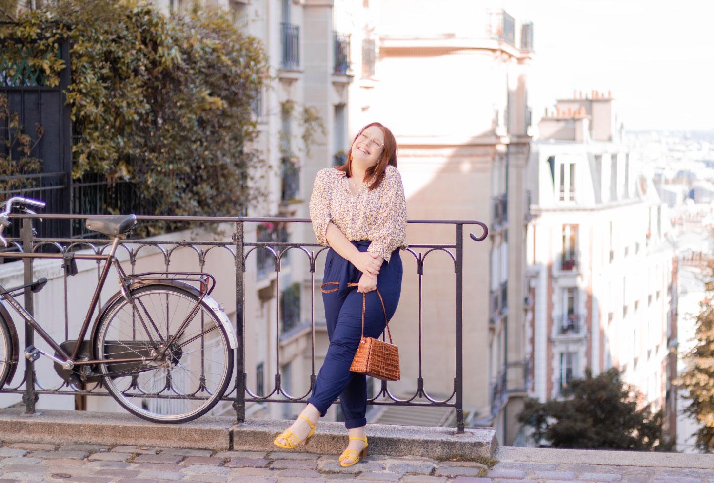 Appuyée le long d'une rambarde devant les escaliers de Montmartre, avec le sourire, le sac Cavale Paris entre les mains