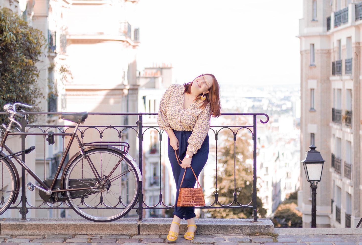 Le long d'une rambarde en métal à côté d'une vieux vélo à Montmartre, avec le sourire, en pantalon bleu fluide et chemisier jaune