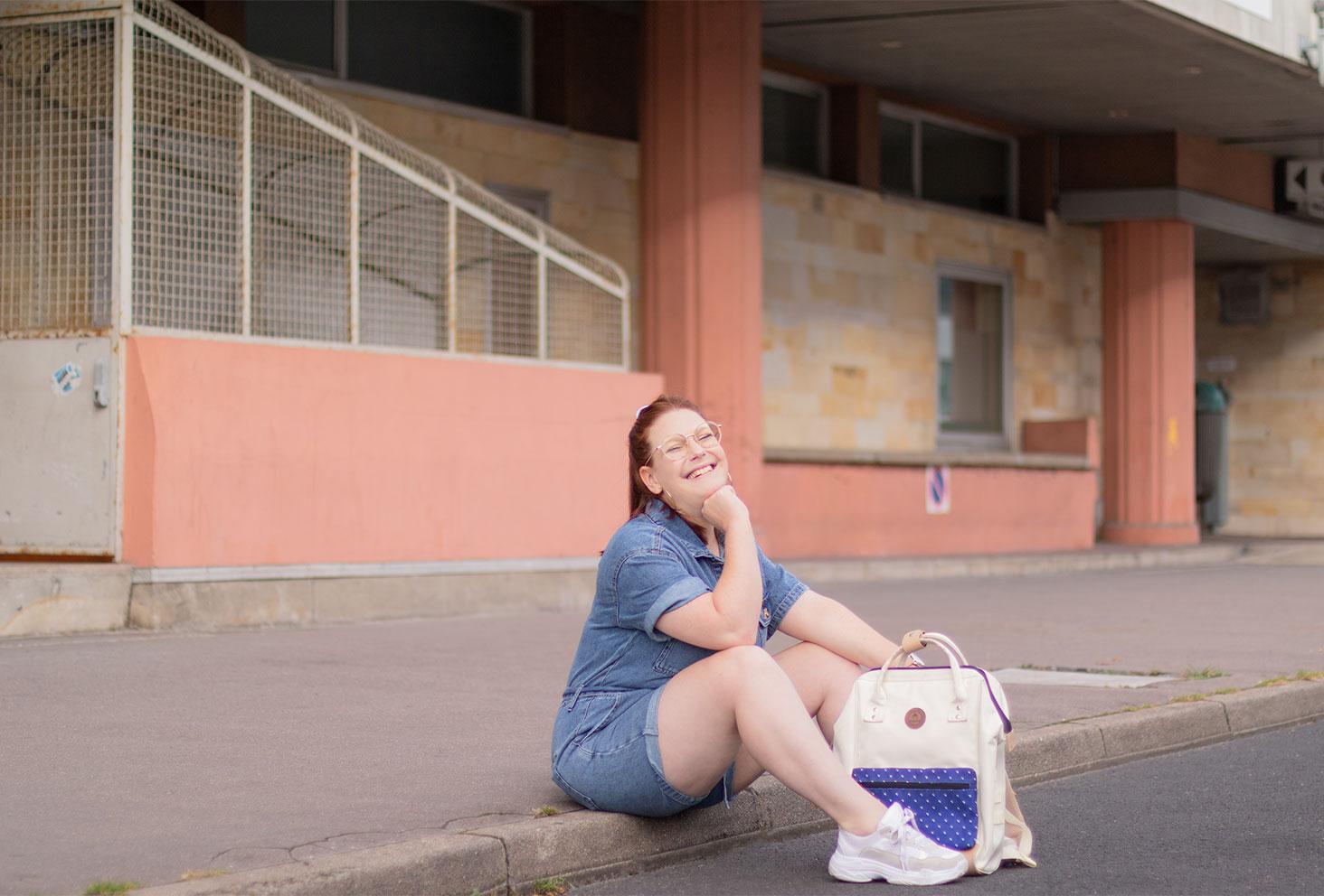 Assise dans la rue en combishort en jean avec un sac à dos et des baskets