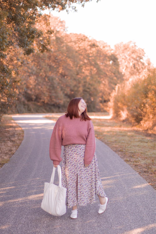 Au milieu des arbres aux couleurs d'automne en longue robe fleurie et pull rose, avec le sourire, un sac blanc dans la main