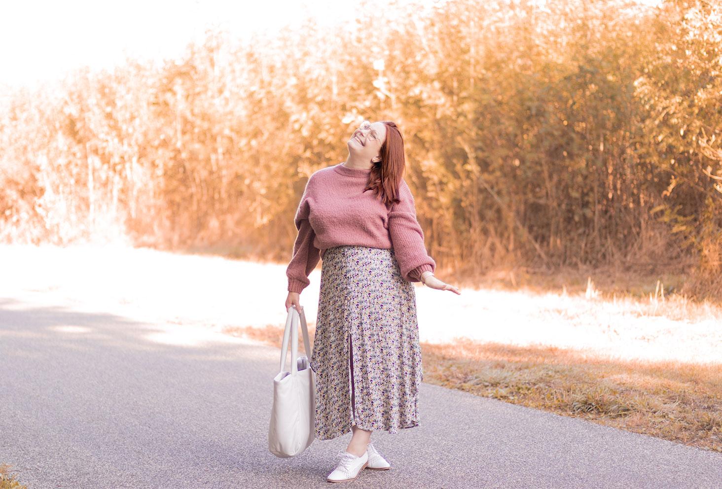 Longue robe fleurie et pull rose pour une rentrée en automne, au milieu des arbres avec le sourire et la tête en l'air