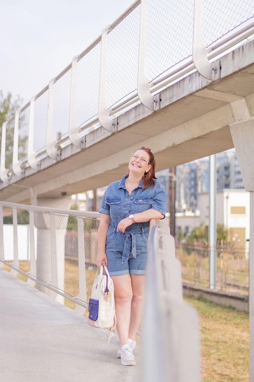 En combishort avec le sourire, sur un pont, un sac à dos dans la main