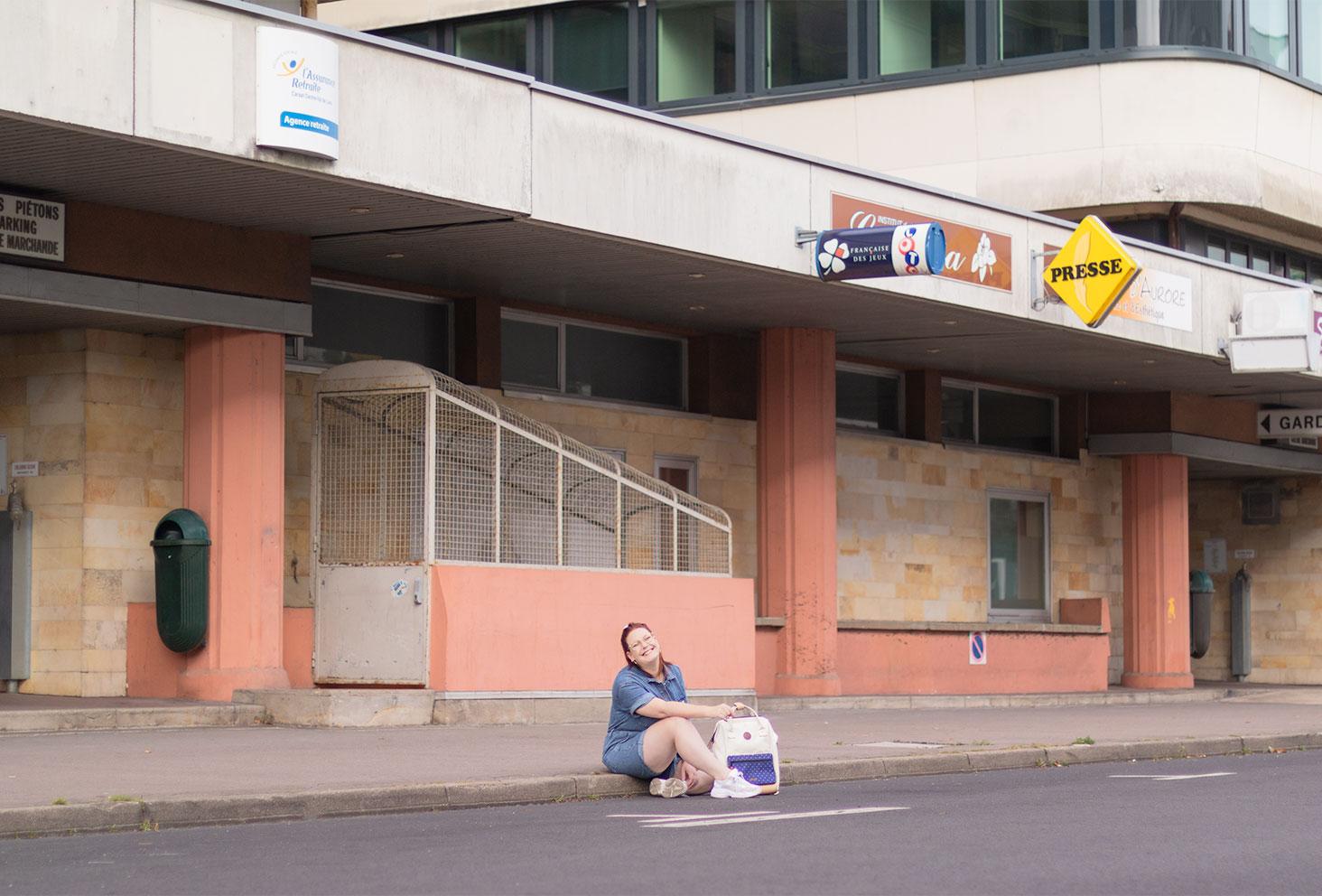 Au milieu de la rue, assise avec le sourire, en combishort en jean