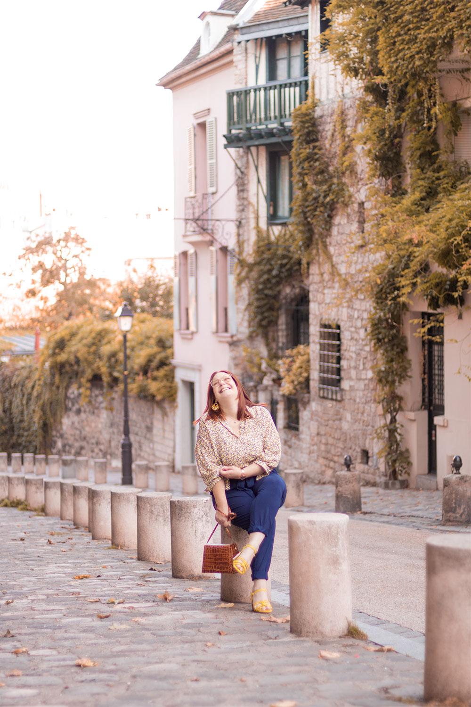 Dans une ruelle de Montmartre avec le sourire, assise sur un plot en béton, le sac Capri de Cavale Paris dans les mains