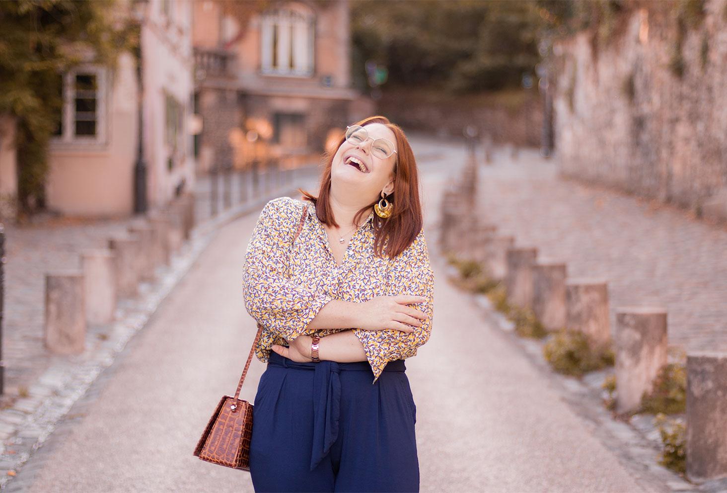 Avec le sourire dans une rue de Montmartre pour la rentrée, en chemisier jaune, un sac Cavale Paris sur l'épaule