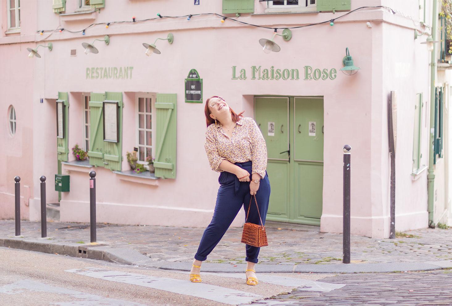 Devant le restaurant La Maison Rose de Montmartre en pantalon Les Lunes et chemisier, avec le sourire, et un sac marron Cavale Paris dans les mains