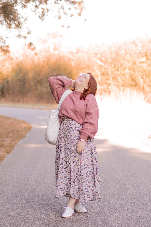 Robe à fleurs et pull rose, avec le sourire, sur un chemin le sac sur l'épaule