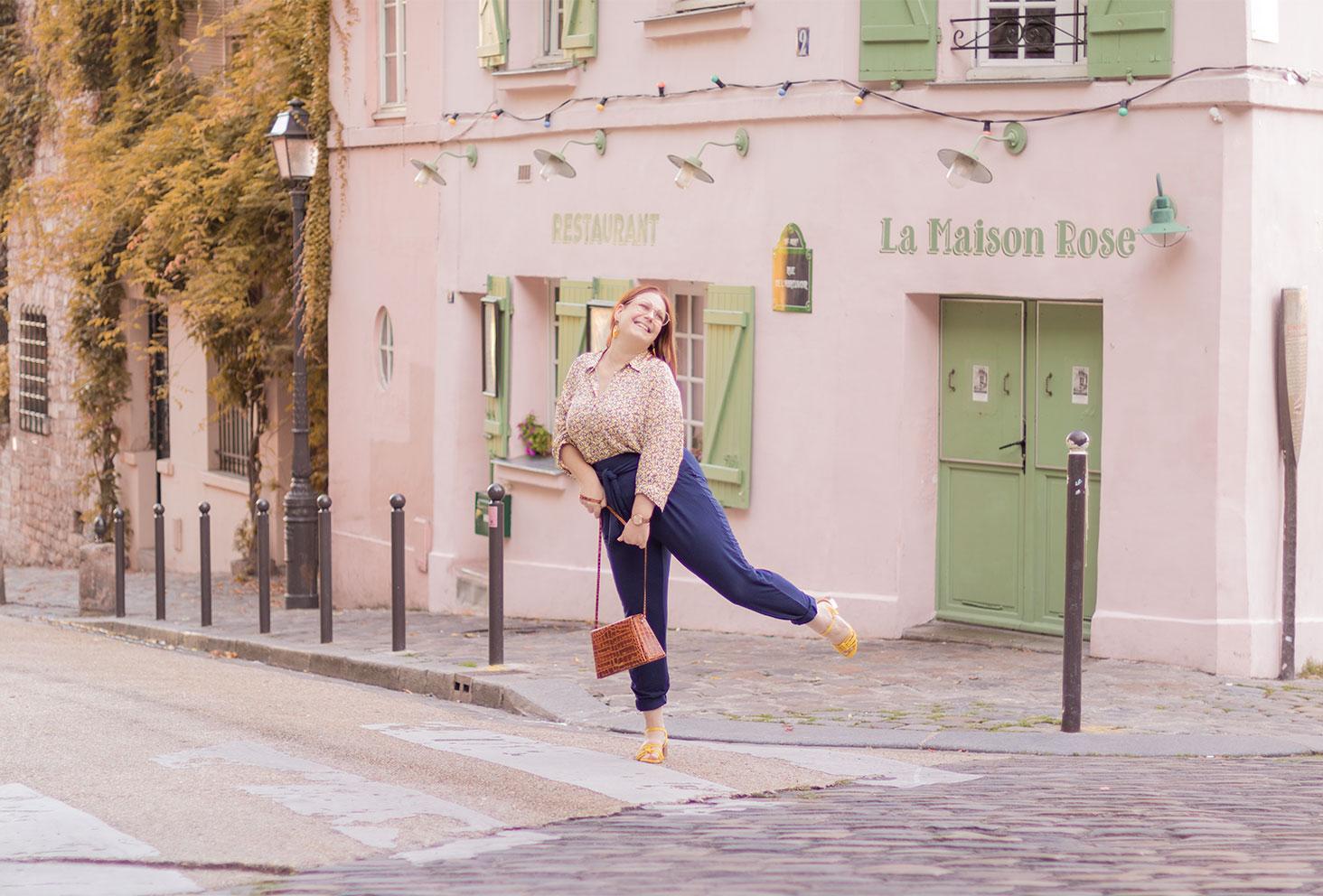 Sur le passage piéton devant la Maison Rose de Montmartre avec le sourire, en pantalon avec un chemisier, un sac à main entre les mains
