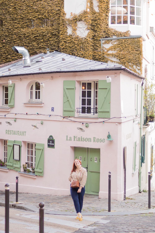 Devant la mythique Maison Rose de Montmartre en chemisier et pantalon