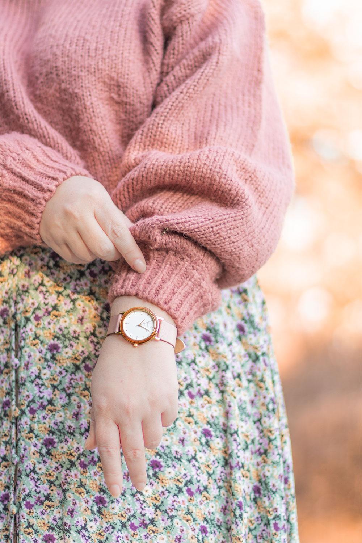 La montre rose Nordic Wood portée avec un pull rose et une robe à fleurs dans les teintes turquoises