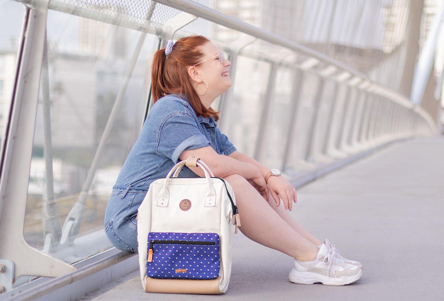 Assise sur un pont avec le sourire, en combishort en jean, un sac à dos posé à côté