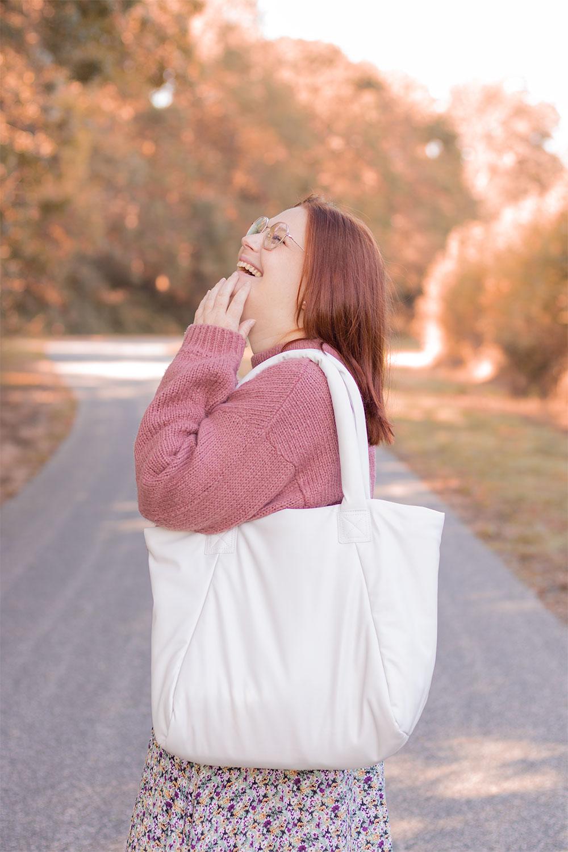 Zoom sur le cabas blanc Vegan H&M porté avec un pull rose et le sourire