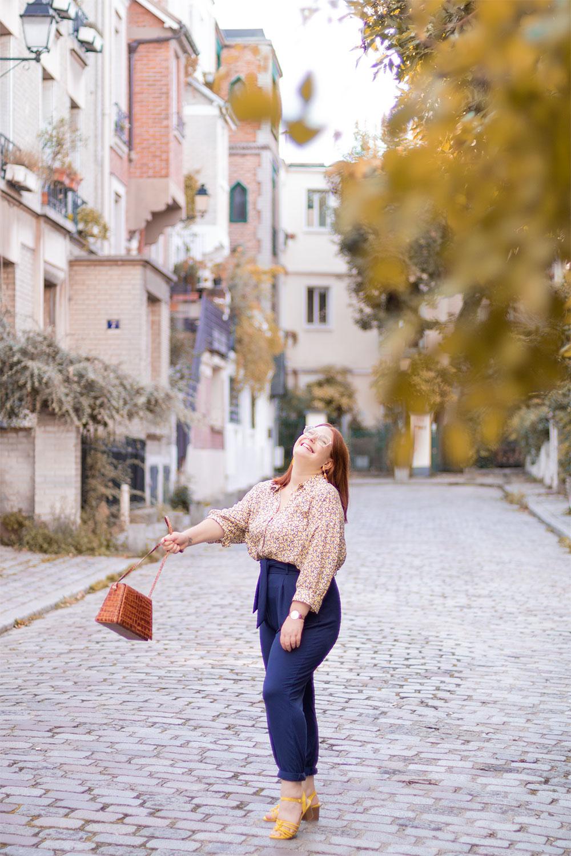 Derrière les arbres dans une rue pavée de Montmartre, avec le sourire, pour faire voler le sac Cavale Paris dans les airs