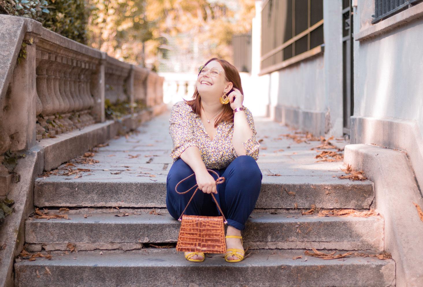 Assise dans des marches de Montmartre avec le sourire, en chemisier citron et pantalon bleu Les Lunes, le sac Cavale Paris dans la main
