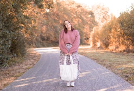 Au milieu d'un chemin boisé avec le sourire, en pull rose et longue robe fleurie, un sac blanc entre les mains