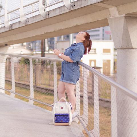 Sur un pont avec le sourire, en combishort en jean appuyée le long de la rambarde, un sac à dos posé aux pieds