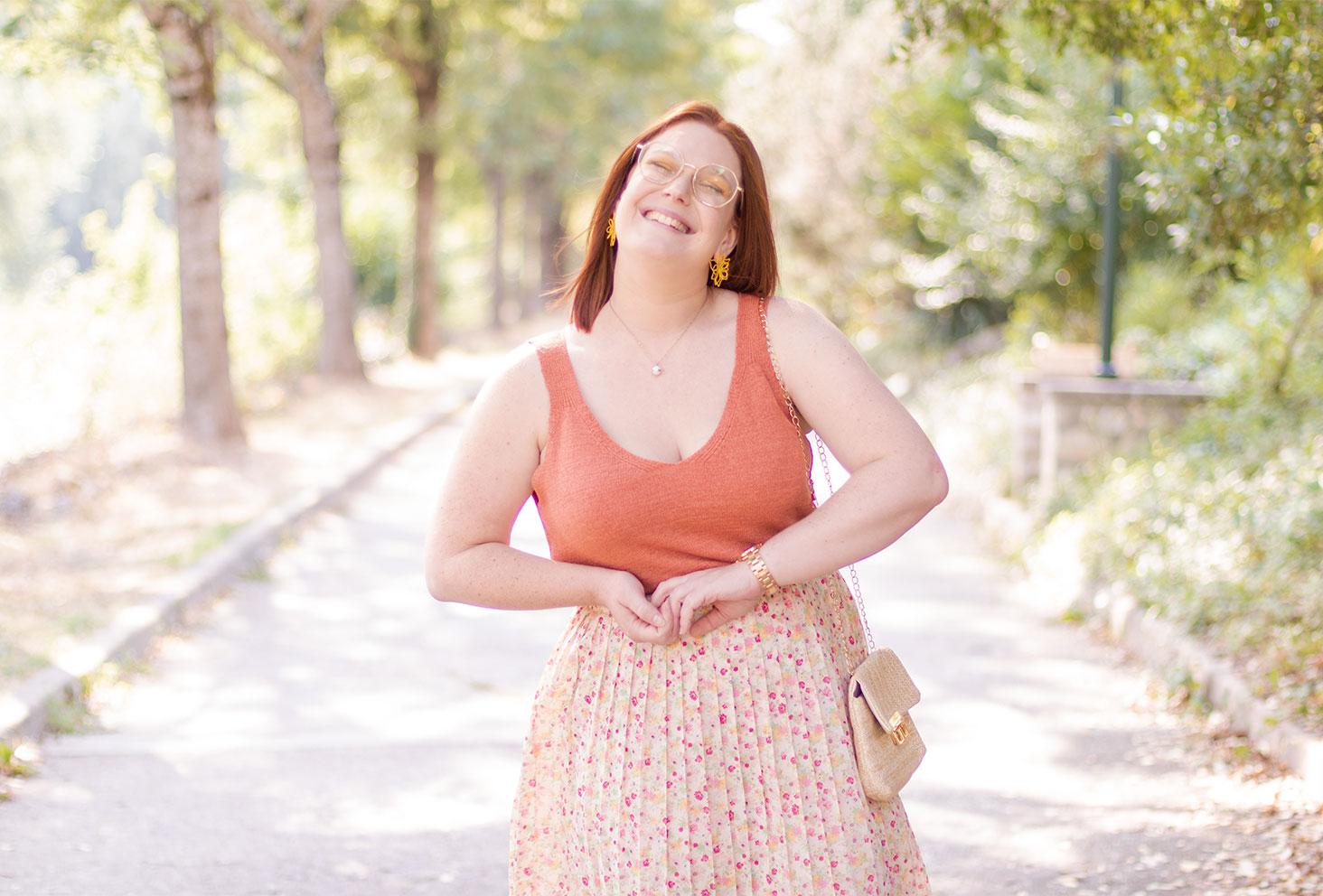 Top orange en lainage porté avec une jupe fluide et fleurie pour la rentrée