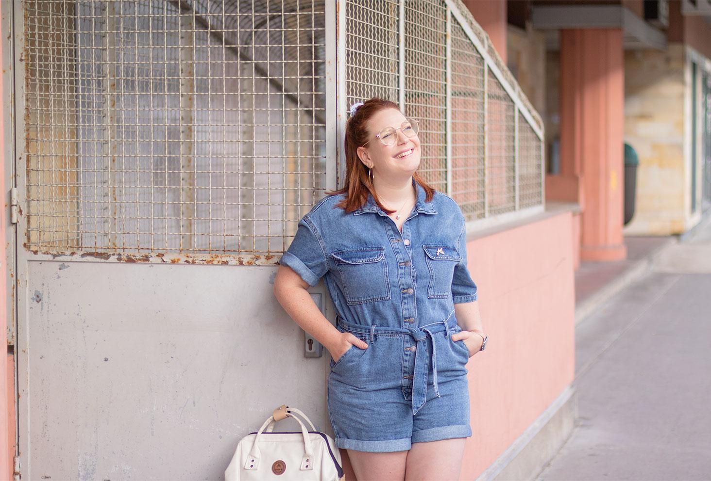 Zoom sur la combishort en jean portée, appuyée le long d'une porte grillagée, avec le sourire et les mains dans les poches