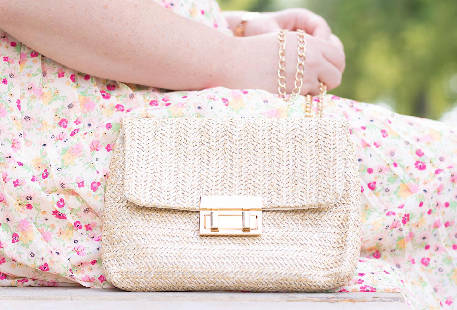 Zoom sur une pochette beige et dorée en paille portée avec une jupe à fleurs