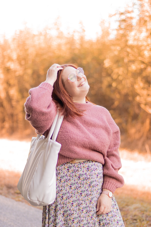 Une main dans les cheveux, au milieu des arbres oranges, en pull rose et robe fleurie avec le sourire