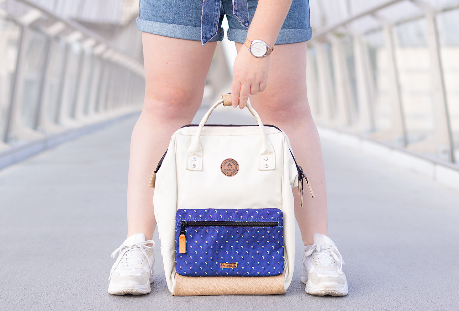 Zoom sur le sac à dos beige et bleu Cabaia, tenu d'une main avec une montre beige Fossil