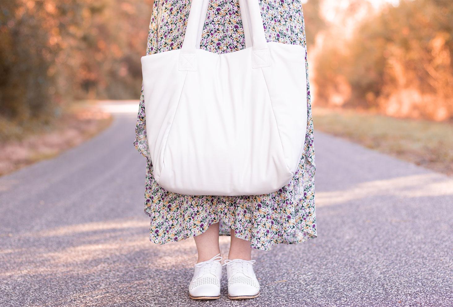 Zoom sur le sac cabas végan blanc H&M, tenu entre les mains devant une jupe à fleurs pastel