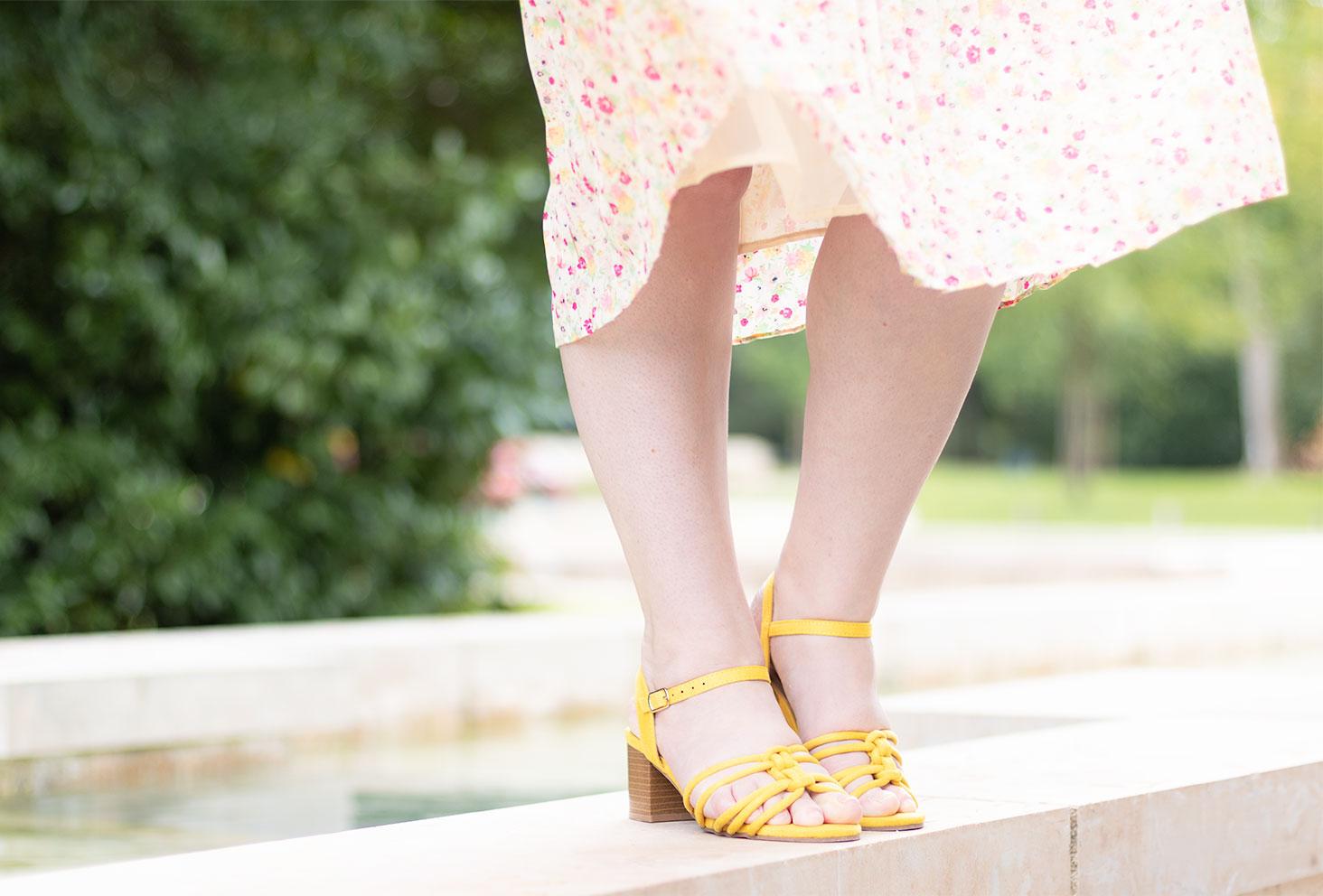 Zoom sur les sandales jaunes à talon portée avec une jupe à fleurs