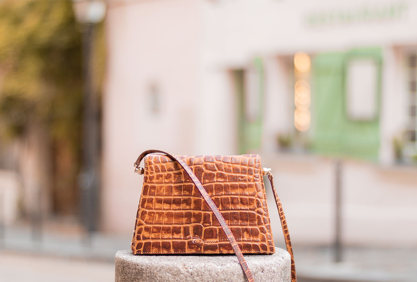 Le sac Capri de Cavale Paris en cuir effet croco marron, posé sur un plot en béton devant la Maison Rose de Montmartre
