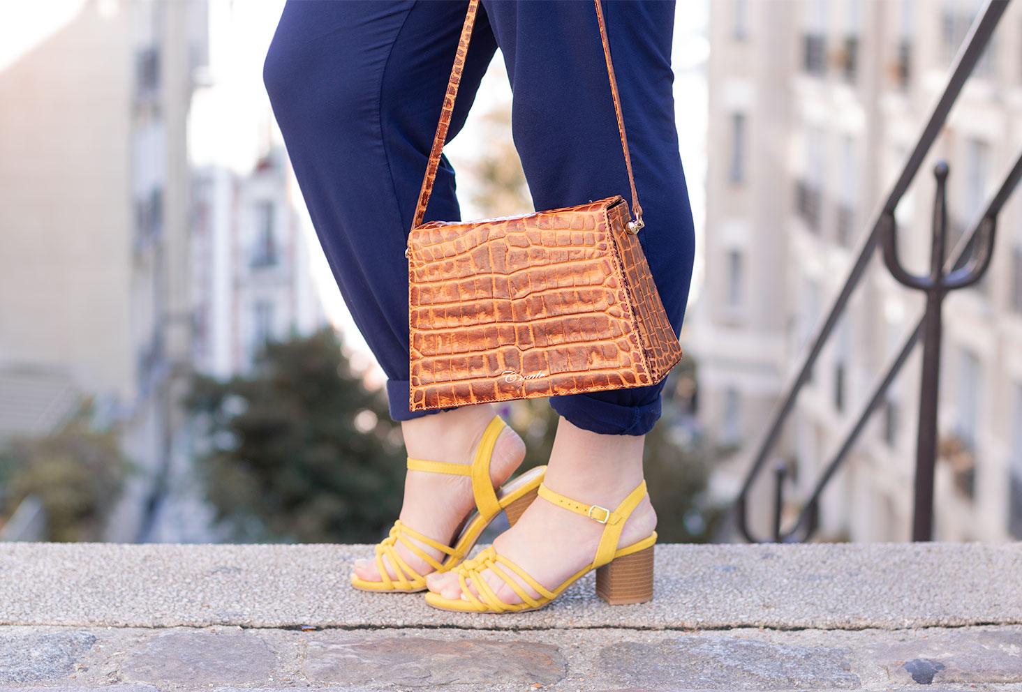 Zoom sur le sac Cavale Paris porté avec une paire de sandales à talons jaune et un pantalon bleu